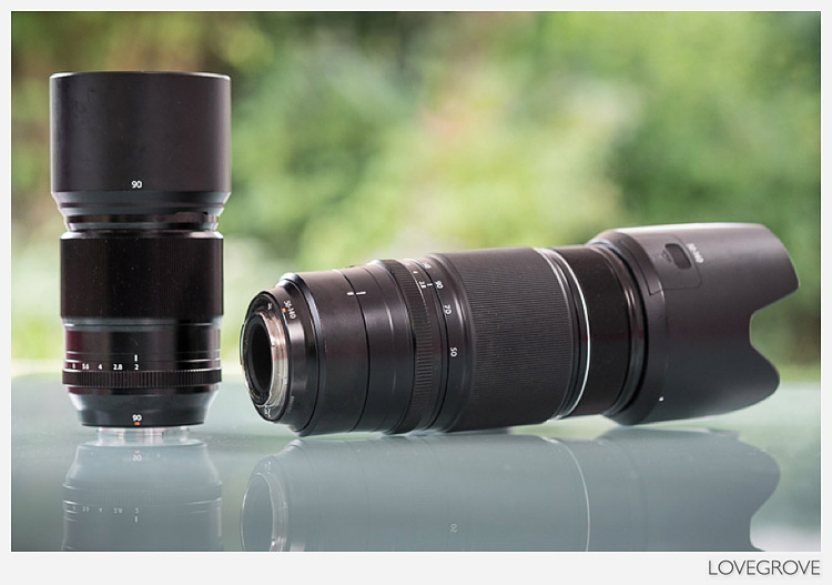 The Fuji XF 90mm f/2 lens on the left is significantly smaller and lighter than the XF 50-140mm lens on the right.
